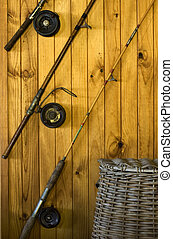 Fishing rods and basket - Three fishing rods on a textured...