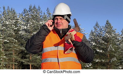 Lumberjack talking on cell phone in forest
