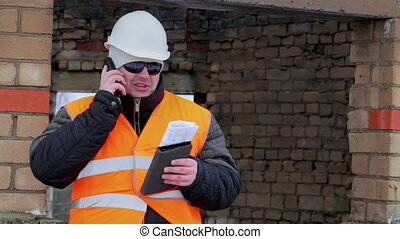 Construction foreman with cell phone and tablet PC