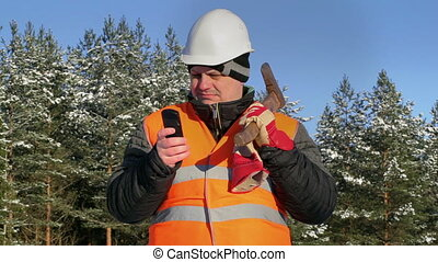 Lumberjack with cell phone in forest
