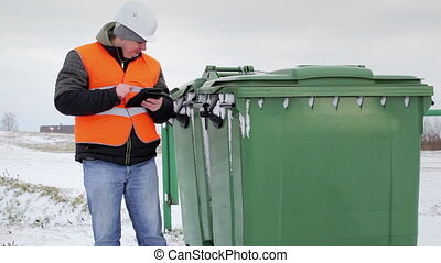 Inspector with cell tablet PC near the garbage containers