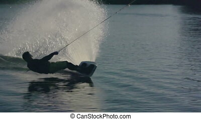 Active Summer Day - Tracking shot of man wakeboarding in...