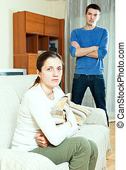 Unhappy young woman against standing man