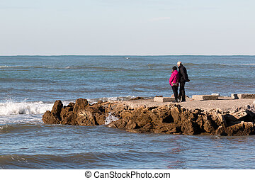 elderly couple enjoy the view on seacoast in winter, sea...