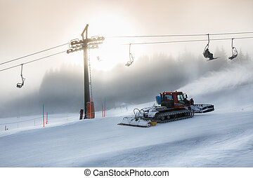 Silhouette photo of snow removal machine working on high ski...