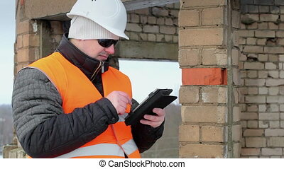 Construction foreman with tablet PC near unfinished building...
