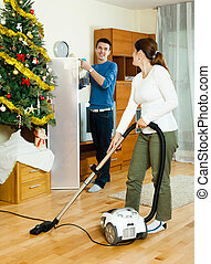 Happy man and woman cleaning with vacuum cleaner in...