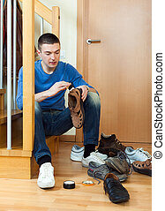 Young man cleaning footwear sitting on the steps at home...