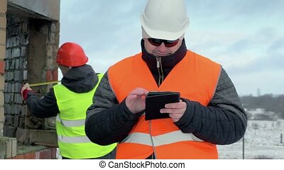 Engineer with tablet PC near unfinished building