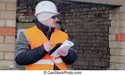 Worker with tablet PC and documentation unfinished building