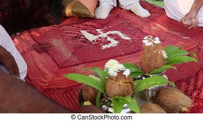 brahmin conducting Indian wedding ceremony making swastika...