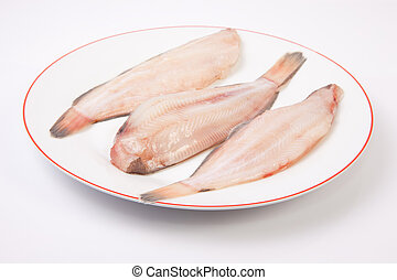 Raw sole fish ready to cook. Plate of three pieces isolated...