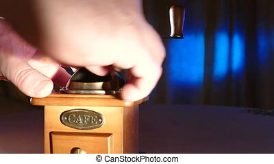 Manual coffee grinder on a blue background, mov
