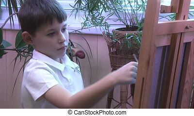 boy draws a picture on the easel