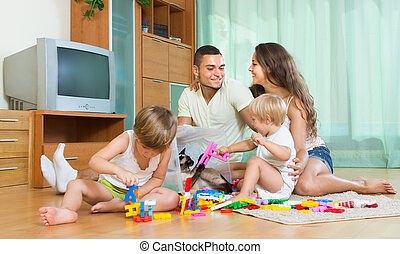 Family of four at home with toys - Smiling young parents and...