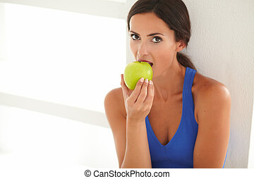 Sporty lady eating fruit for healthcare