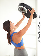 Latin woman raising a weight scale