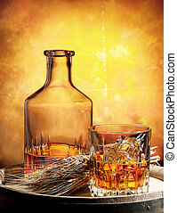 Glass of whiskey decanter and ears of wheat on a wooden...