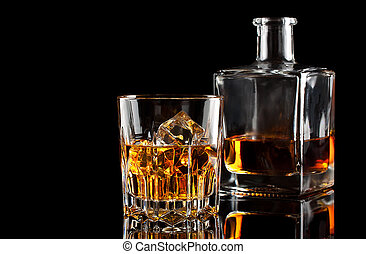 Glass of whiskey with ice and a square decanter isolated on...
