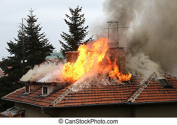 Burning house roof - A house roof on fire and smoke.