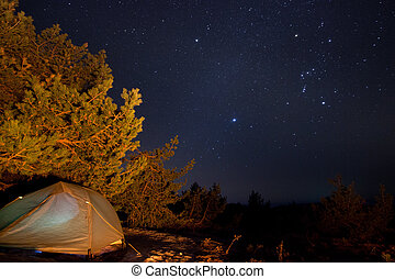 milky way above the mountains with tent highlighted by...