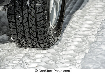 Winter tyre on the road with snow