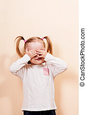 Peek A Boo - Little girl with ponytails playing peek a boo,...