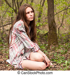 Young beautiful sexy girl in a shirt in the woods or park.