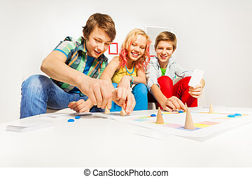 Girl and two boys playing table game at home - Girl and two...