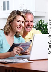 Senior couple at home with computer - Senior couple looking...