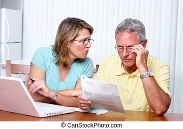 Senior couple at home with computer. - Senior couple looking...