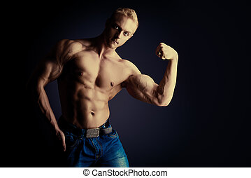 demonstrating - Muscular bodybuilder man posing over dark...