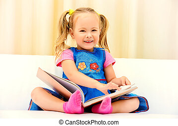 funny book - Pretty little girl sitting on a sofa and...