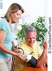 Blood pressure measuring. - Senior woman and man measuring...