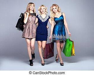 Smiling girls shopping - Three beautiful happy blonde woman...