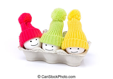 funny eggs - smiling - three eggs in a egg box wearing red,...