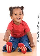 Adorable african baby sit over wooden floor