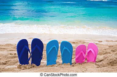 Color Flip flops next to ocean
