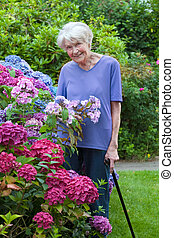Old Woman with Cane Posing Beside Pretty Flowers - Smiling...