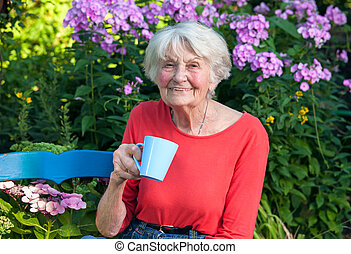 Happy Grandma Having a Coffee at the Garden - Close up Happy...