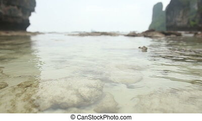 sea stony coast with very transparent water against island...