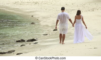 bride and groom walk along beach under rain