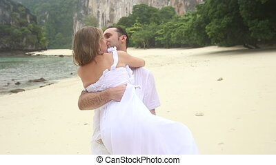 groom carries blonde bride in arms and kisses