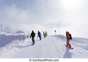 Skiers and snowboarders going down the slope. - Skiers and...