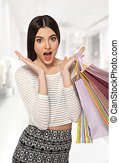 Shopping young beautiful happy girl with colored bags