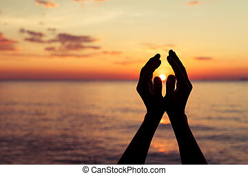 silhouette of female hands during sunset