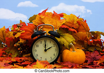 Daylight savings - Fall coloured leaves with a black clock...