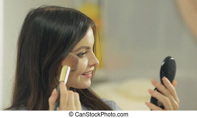 Close-up of a cute brunette doing make-up looking in the...