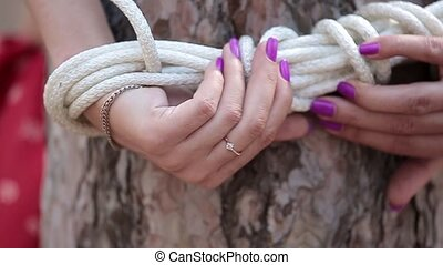 Woman with tied up hands to the tree - Young woman in red...