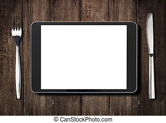 black tablet pc on dark wooden table with fork and knife -...